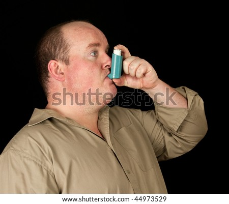 photo of fat male with inhaler asthma on black background - stock photo