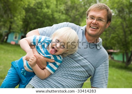 Photo of father holding his son showing tongue - stock photo