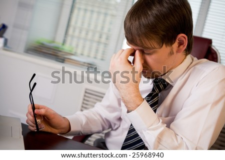 Photo of fatigue man with his eyeglasses off keeping his hand near face after hard working day - stock photo