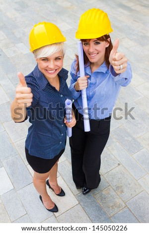Photo of female constructors making positive thumb gesture while smiling