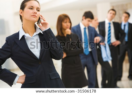 Photo of female employee speaking on the phone with smile on background of businesspeople