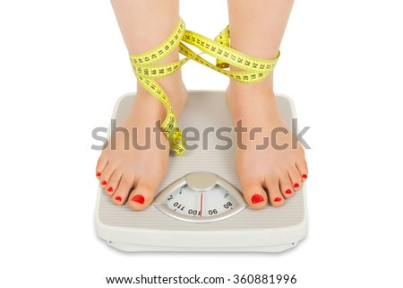 Photo of female foot on bathroom scale tied with tape meter isolated on white background - stock photo