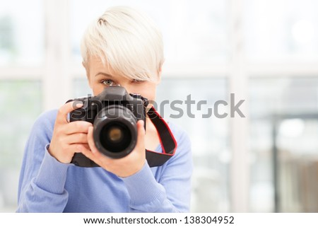 photo of Female photographer with DSLR at home sitting on the floor - stock photo