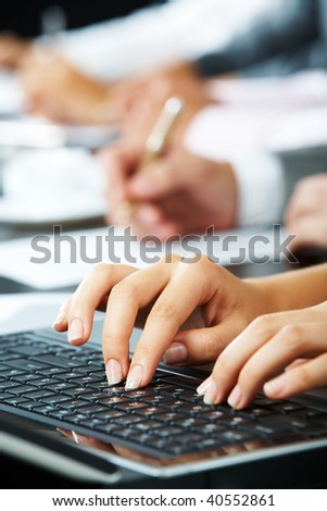 Photo of female?s hands touching keys of laptop during briefing on background of human hands - stock photo