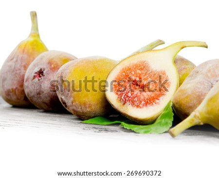 Photo of figs with slice and leaves on wooden board with white space