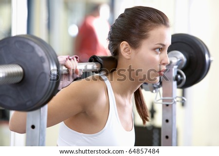 Photo of fit brunette practicing weightlifting