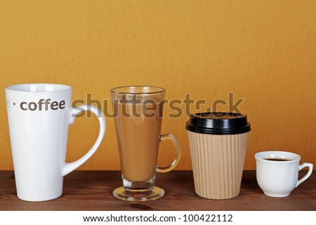 Photo of four types of coffee including a latte, espresso, mocha and cappuccino in different styles of cups, mugs and containers. - stock photo