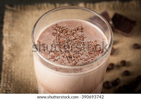 Photo of fresh Made Chocolate Banana Smoothie on a wooden table with coffee and spices. Selective focus. Milkshake. Protein diet. Healthy food concept. Drink, coffee beans, chocolate,  - stock photo