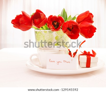 Photo of fresh red tulip flowers in beautiful vase on table, cup of tea, little white gift box with ribbon, festive postcard with ladybird decorations, home interior, happy mothers day, love concept - stock photo