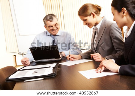 Photo of friendly business group sitting at the desk in the office and planning work