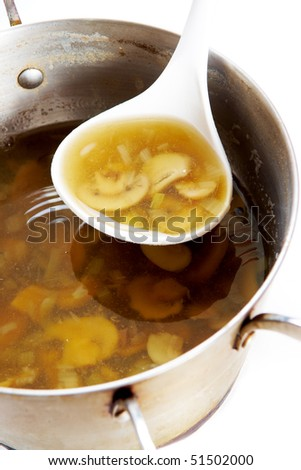 Photo of fungoid soup in pan and ladle