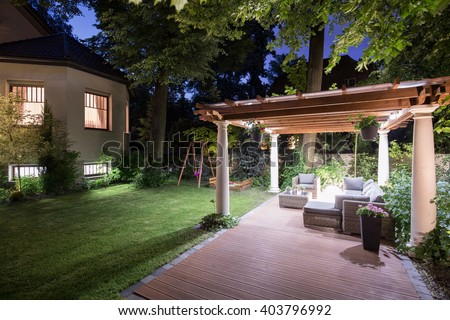 Photo of garden with covered patio at night - stock photo