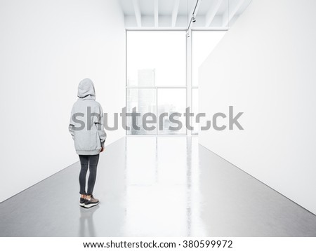Photo of girl in empty contemporary gallery looking at the blank white canvas. Big windows, spotlights, concrete floor. Horizontal, mockup - stock photo