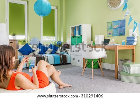 Photo of girl sitting on sack chair in teenager room - stock photo