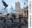 Photo of girl-traveller surrounded flock of birds in the square - stock photo