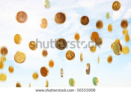 photo of golden coins raining from the sky - stock photo