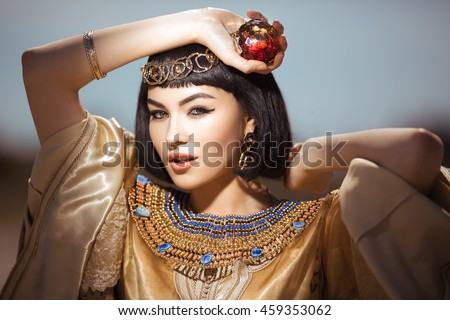 Photo of gorgeous woman with Cleopatra makeup, closeup portrait of beautiful female with stylish haircut agaist, young lady wearing fashionable golden necklace and holding magik ball outdoor, beauty - stock photo