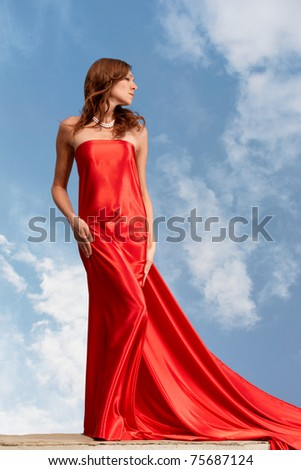 Photo of graceful female folded in bright red silk shawl with cloudy sky at background - stock photo