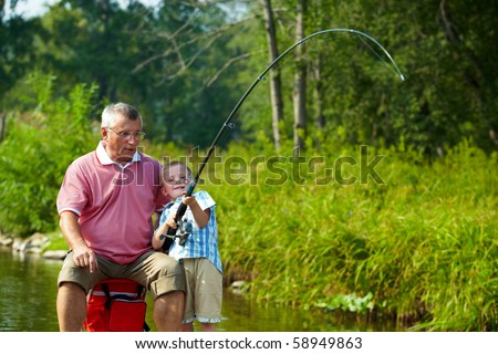 Photo of grandfather and grandson fishing on weekend - stock photo