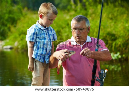 Photo of grandfather and grandson looking at fish caught by them - stock photo