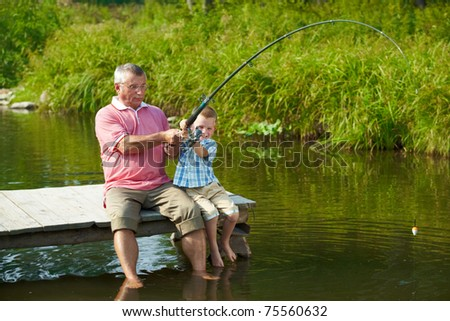 Photo of grandfather and grandson pulling rod while fishing on weekend - stock photo