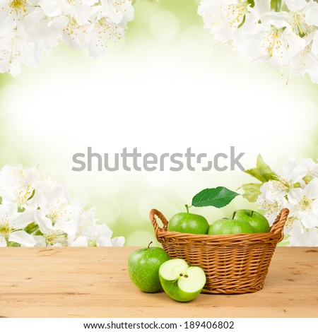 Photo of green apples in basket with apple blossom background - stock photo