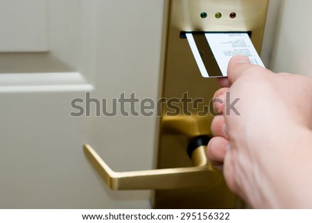 Photo of hand inserting a key card into an electronic hotel door security lock to unlock the door. - stock photo