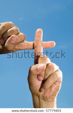 photo of hands, fingers that form a cross against the blue sky - stock photo