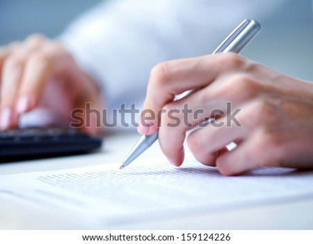 Photo of hands holding pen under document  and pressing calculator buttons - stock photo