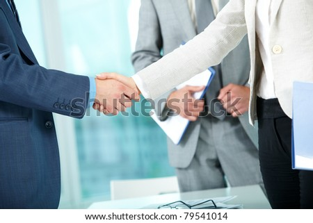 Photo of handshake of business partners after striking deal on background of man - stock photo