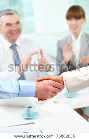 Photo of handshake of business partners after striking deal on background of two partners applauding - stock photo
