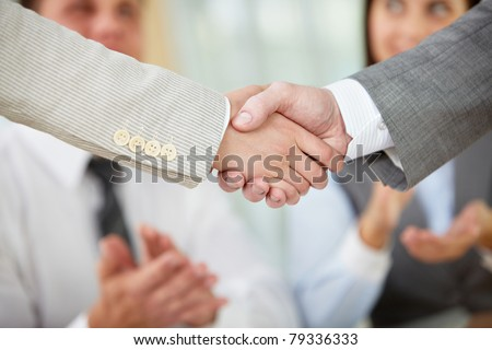 Photo of handshake of business partners on background of two partners applauding - stock photo