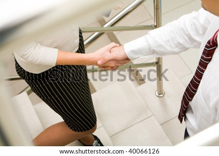 Photo of handshake of business partners while they standing on stairs