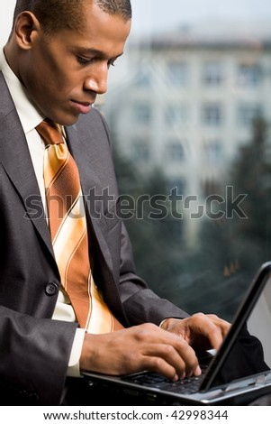 Photo of handsome employee working in office with laptop in front - stock photo