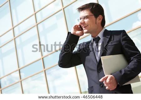 Photo of handsome employer speaking on mobile phone