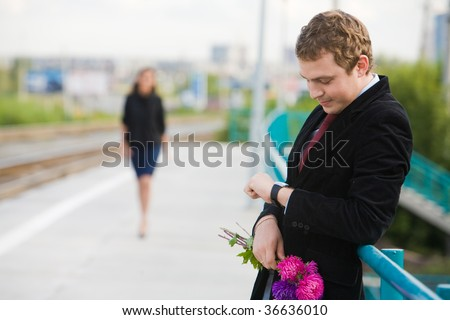 Photo of handsome guy with aster bunch waiting for his girlfriend outside