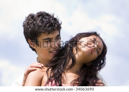 Photo of handsome man embracing tenderly beautiful woman on background of sky