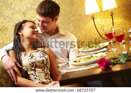 Photo of handsome man embracing with love his girl in the restaurant - stock photo