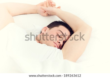 Photo of handsome man sleeping on soft white pillow,  domestic atmosphere