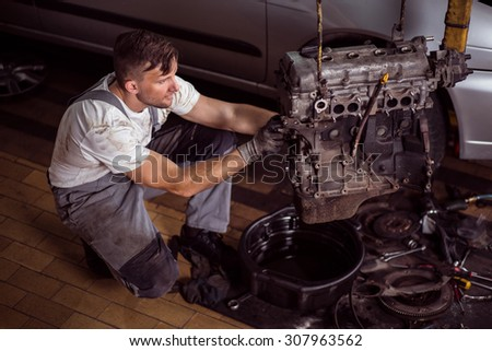 Photo of handsome service station worker repairing motor car