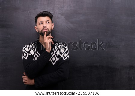 Photo of handsome young stylish man on blank chalkboard background. Man thoughtfully looking aside