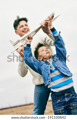 Photo of happy boy and his father playing together outdoors - stock photo