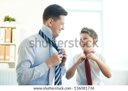 Photo of happy boy and his father tying neckties - stock photo
