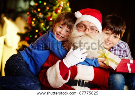 Photo of happy boy embracing Santa Claus with cute kid near by