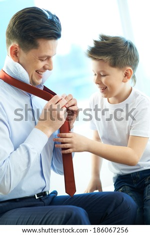 Photo of happy boy looking at his father tying necktie - stock photo