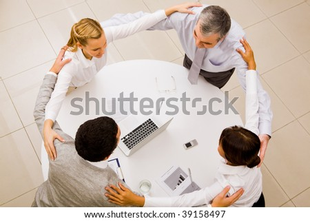 Photo of happy business partners embracing each other over workplace - stock photo