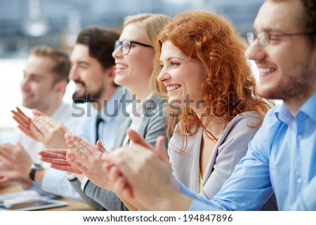 Photo of happy business people applauding at conference, focus on redhead female - stock photo