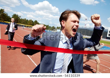 Photo of happy businessman crossing finish line during race - stock photo