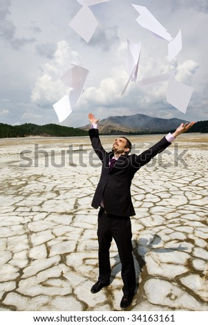 Photo of happy businessman standing on dry ground and throwing papers upwards - stock photo