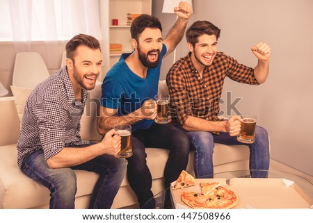 photo of happy cheerful men  holding glass of beer and watching tv - stock photo